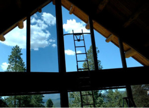 Solar control window film installation job in progress at Colorado Springs home second story windows with ladder